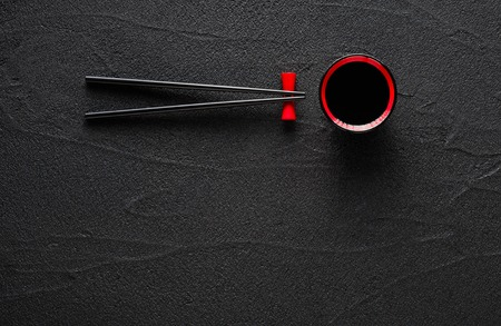 black stone: Chopsticks and bowl with soy sauce on black stone background Stock Photo