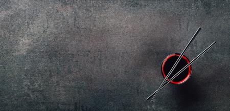 箸と織り目加工の背景に醤油丼 写真素材