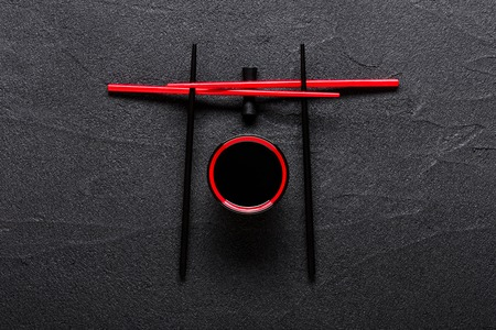 Chopsticks and bowl with soy sauce on black stone background Stock Photo