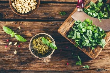 Pesto saus en ingrediënten op oude houten tafel, vintage stijl