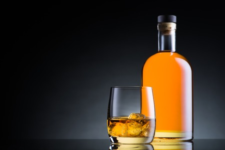 Whiskey glas en fles op zwarte glasoppervlakte Stockfoto