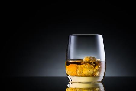 黒のガラス表面のウィスキー グラス 写真素材