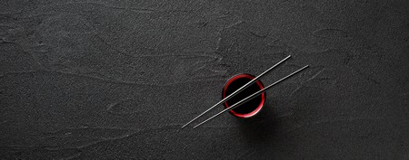 Chopsticks and bowl with soy sauce on black stone background Standard-Bild