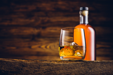 Whisky glas en fles op de oude houten tafel