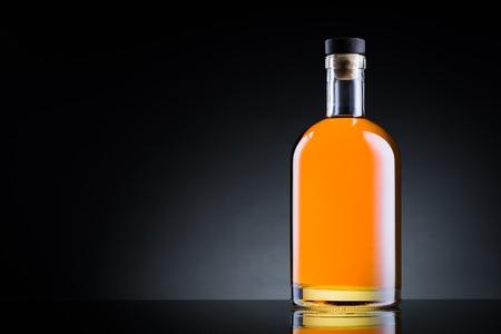 botella de licor: Botella de whisky en la superficie de cristal negro Foto de archivo