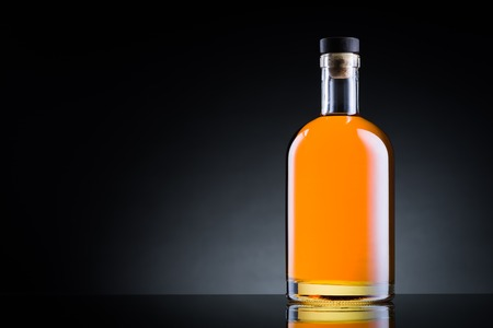 Whiskey bottle on black glass surface