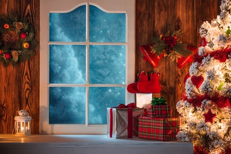 Christmas scene with tree gifts and frozen window in background