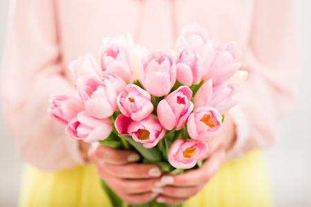 Bos van tulpen in de handen van de vrouw, ondiepe dof. Stockfoto