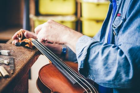 Luthier reparatie viool in zijn atelier