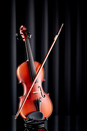 Close up of a violin on glass surface and black background