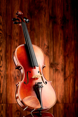 Close up of a violin on glass surface and wooden background