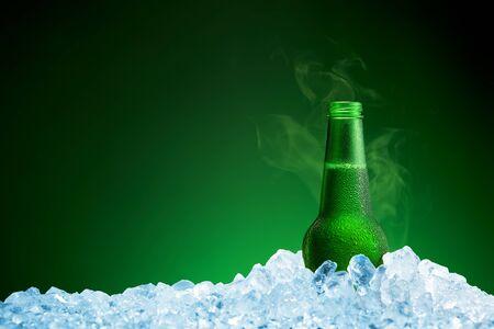 Fles koud bier in ijs op groene achtergrond
