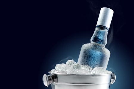 Bouteille de vodka froide dans un seau de glace sur fond noir