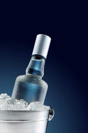 Fles koude wodka in emmer ijs op donkere achtergrond Stockfoto