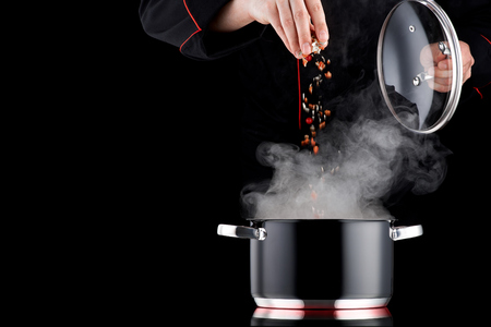 전문 제복을 입은 현대 요리사가 김을 내뿜는 냄비에 양념을 더한다.