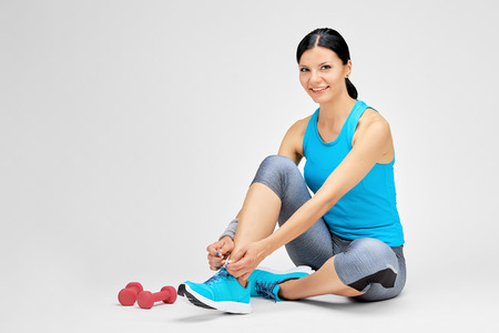 Fit woman tying shoelace at the gym, fitness studio concept Stock Photo