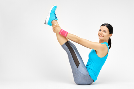 rocker girl: Smiling woman doing stretching pilates exercises at the gym, fitness studio concept