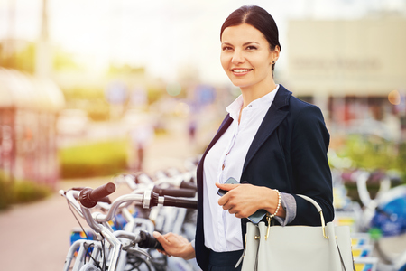 Smiling business woman rent a city bike Stock Photo