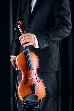 Violinist with elegant suit taking a violin