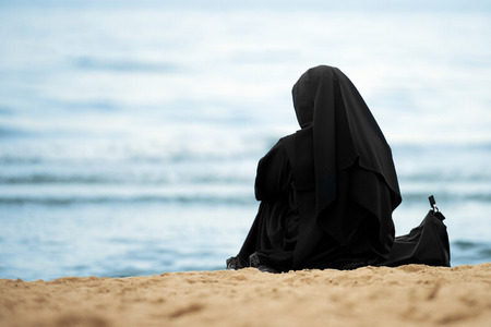 Muslim woman with black clothes sitting on the beach