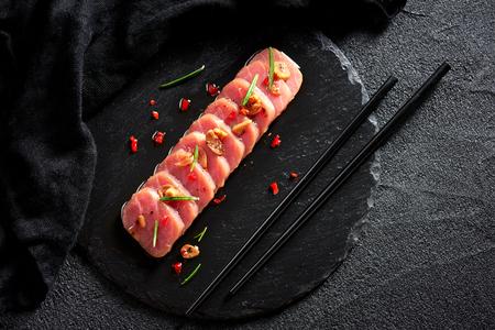 검은 슬레이트 접시에 고추와 로즈마리 오일과 참치 스테이크