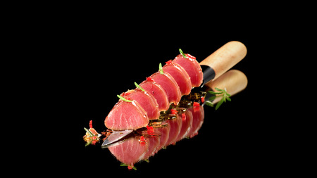 Tuna steak in oil with chilli and rosemary served on knife