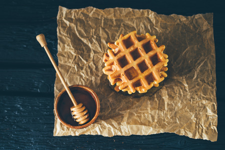 Belgian waffle and bowl of honey on dark wooden table Zdjęcie Seryjne