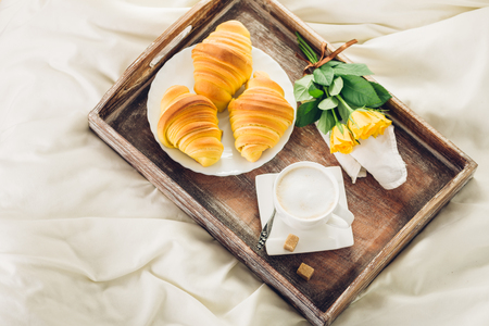 Coffee, croissant and flowers on bed top view