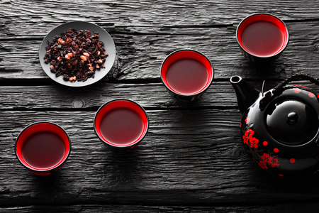 Cups of tea and teapot on black wooden table