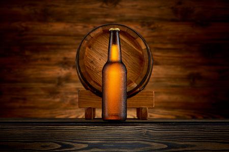 Bottle of cold beer and old barrel on wooden background