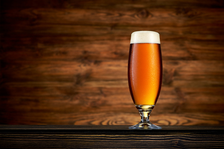 Glass of cold beer on wooden background