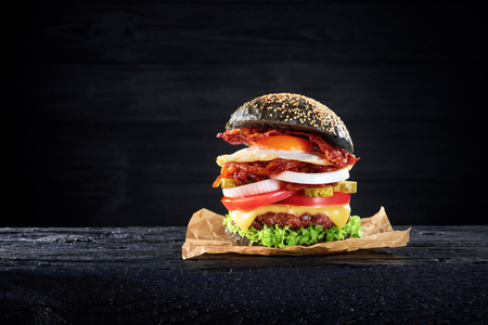 Black burger with egg and bacon on the wooden table
