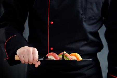 Sushi gedient auf japanischem Messer in der Chefhand