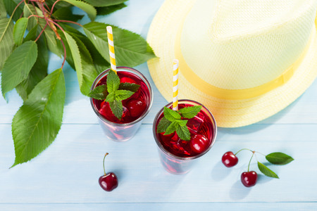 Glass of cherry juice on blue wooden table
