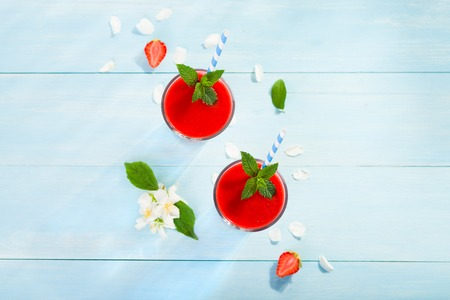 Strawberry smoothie and flower petals on blue background top view