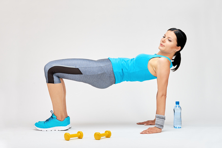 Brunette woman doing stretching exercises at the gym, fitness studio concept Zdjęcie Seryjne