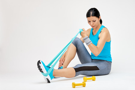 Brunette woman doing exercises with rubber band, fitness studio concept