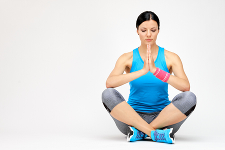 Brunette woman meditating after exercise, fitness studio concept