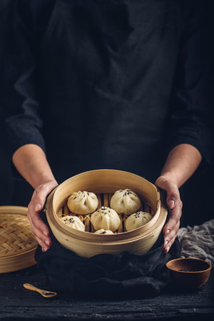 Woman presenting dim sum dumplings in steamer