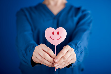 Woman hand giving pink heart shaped lollipop with smile on blue background