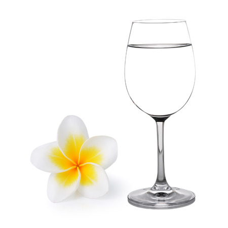Glass of water and Tropical flowers frangipani (plumeria) photo