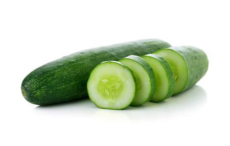 Komkommer en plakjes geïsoleerde over witte achtergrond. Stockfoto