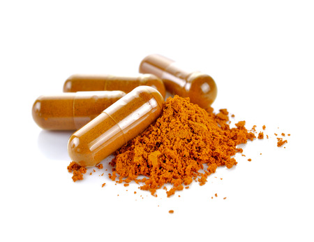 Tumeric powder capsules on white background Stok Fotoğraf