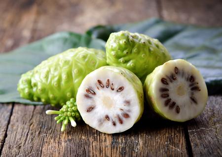 木製の背景のノニ果実