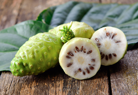 noni fruit on wooden background Banco de Imagens