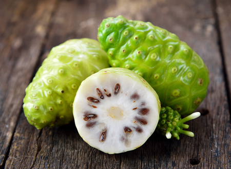 noni fruit on wooden background 스톡 콘텐츠