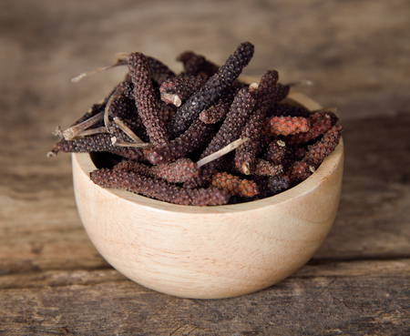 Long pepper or Piper longum on wooden table Stock Photo