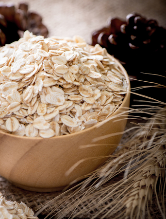 Rolled oats (oat flakes), milk and golden wheat ears on wooden background. Stok Fotoğraf