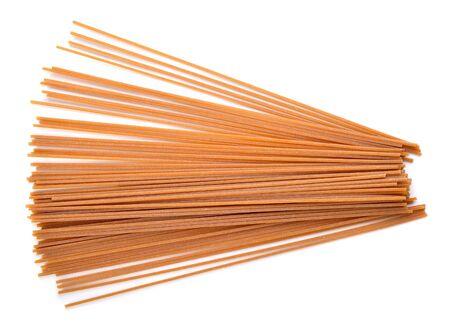 Whole wheat spaghetti on white background.