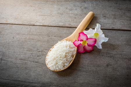 homeware: Rice on Wooden Spoons on wooden background and pink , white flower, still life